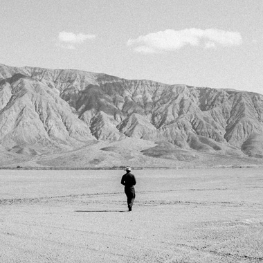 A man walking across a dry lake bed
